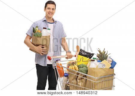 Young man posing with a shopping bag and a shopping cart full of groceries isolated on white background