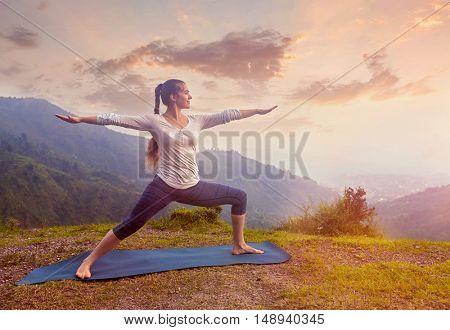 Yoga outdoors - sporty fit woman doing Ashtanga Vinyasa Yoga asana Virabhadrasana 2 Warrior pose posture in mountains