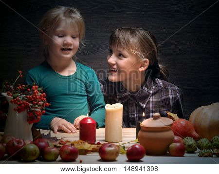 Children are prepared to meet the autumn holiday Halloween. Two sisters at the table. Pumpkin rowan tree ornaments and holiday candles. Laughter joy emotion