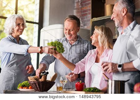 Fully satisfiied. Old parents preparing a meal while their daughter and her husband visiting them