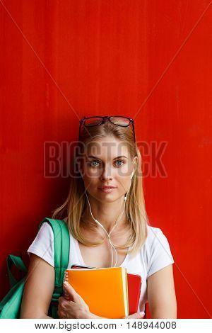 Young woman with sunglasses and headphones on background blank red Wall