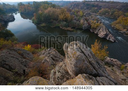 Picturesque river bend in autumn season. Famous Integral riffle of Southern Bug river. Rocks and highly coloured trees in foreground.
