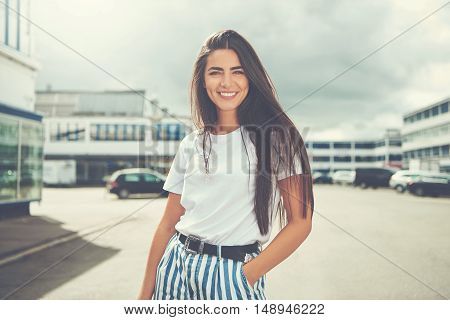 Cute young adult woman with long hair posing in striped pants black belt and hand in pocket outdoors in parking lot