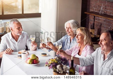 Guests sitting at kitchen table drinking champagne