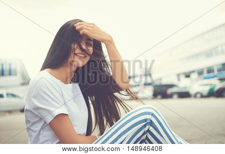 Woman seated on curb has her hair blown by wind as cars park nearby in front of office building
