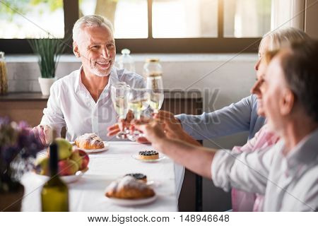 Good taste. Happy and smiley middle aged people rasing glasses with wine