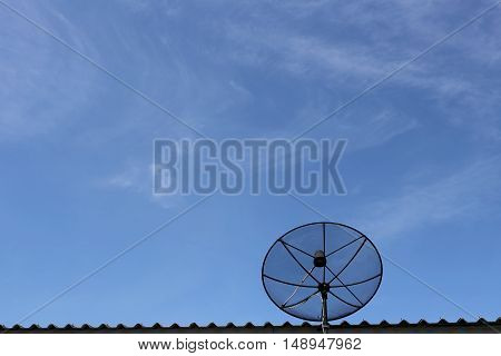 Black Satellite dish on roof in blue sky background and communication technology network tool.