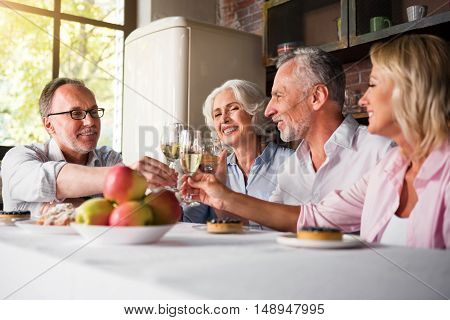 Memorable. Four smiley good-looking people raising glasses with sparkling champagne in the kitchen