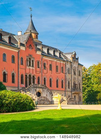 Sychrov Castle with typical pink facade. Neo-Gothic style chateau with beautiful english style park. Bohemian Paradise, Czech Republic