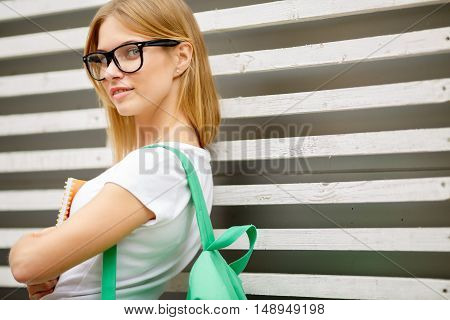 Young woman with backpack standing by fence