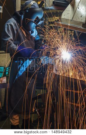 worker with protective mask welding metal in the automotive parts industry