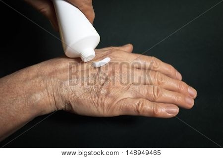 Cream for hands over a dark background. Cosmetic medicine concept.