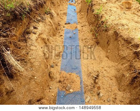Trench With Blue Plastic Protection Tape. Marked Of  Cables Under Clay During Building Of  Internet