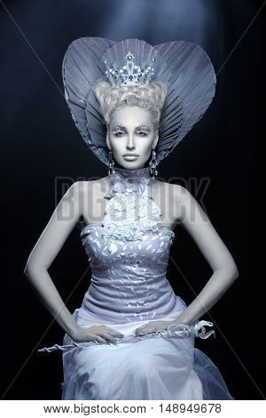 Portrait of beautiful young woman dressed as winter queen. Creative makeup. Over dark background. Copy space.