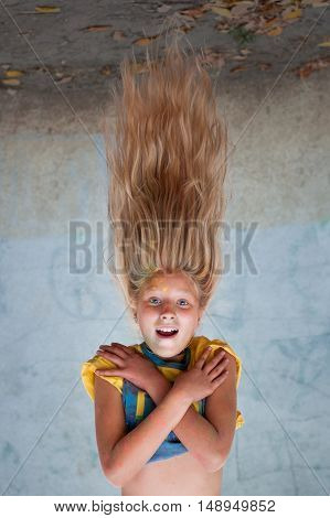 girl with long hair hanging upside down in the summer