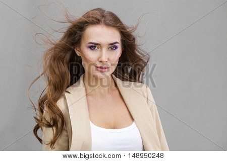 Make Up. Beautiful young woman. Healthy Long Curly Hair. Isolated on gray background