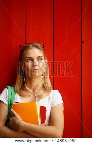 Girl in headphones looking to side on background of Brown fence