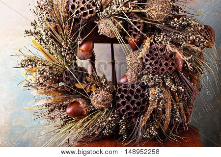 Festive autumn wreath with acorns and fall leaves on an antique chair