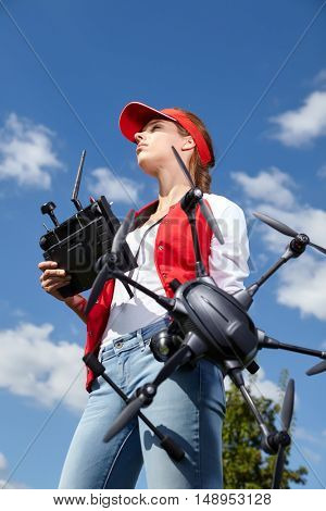 A woman is standing and holding drone over sky