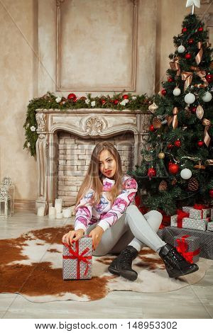 Christmas Gift. New year celebration. Beautiful holdiay decorated room with Christmas tree with presents under it. New Year and Christmas concepts. Beautiful girl sitting near New Year tree.