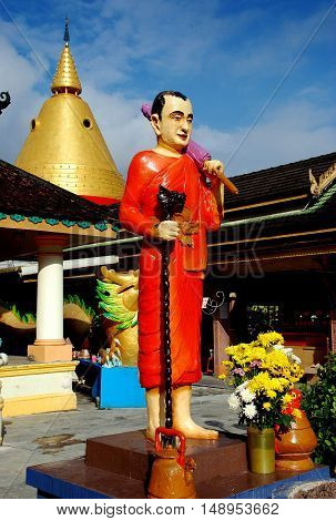 Georgetown Malaysia - January 9 2008: Statue of an orange robed monk with walking stick and a parasol at the Buppharam Thai Buddhist Temple