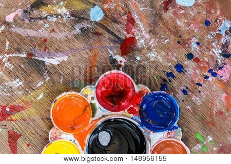 wooden art palette with paint and brushes close up