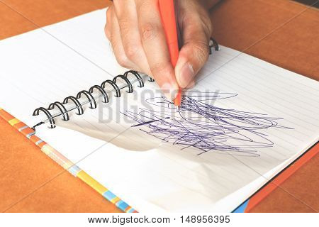 female hands with pen writing labyrinthine on notebook
