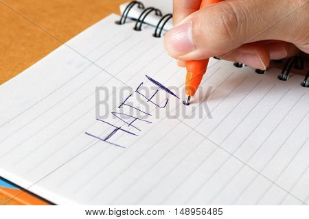 Woman's hand with pen writing word Hate on notepad.