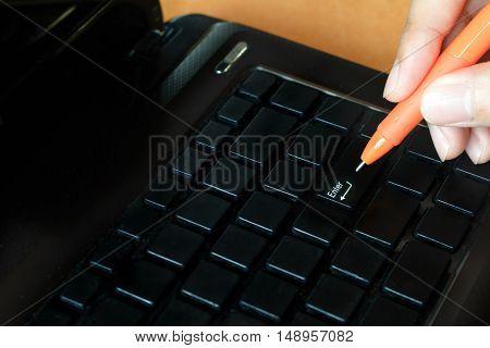 Woman holding pen with laptop pressing enter button soft focus.