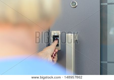 Woman Using Scanner To Read Her Thumb Print