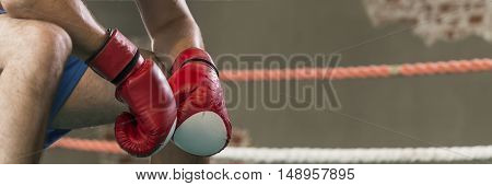 Close-up of a boxer who squats in the ring with boxing gloves