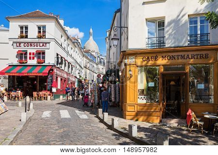 Paris France - July 06 2016: The charming quarter of Montmartre hill near basilica Sacre Coeur with traditional french cafes and art galleries. Montmartre is one of the most visited landmarks in Paris