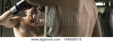 Focused and confident boxer in boxing gloves looking at colleague with a towel