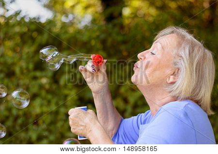 Attractive Senior Woman Blowing Soap Bubbles
