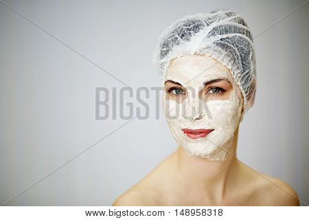 Portrait of smiling woman with cosmetic mask on face and mesh hair cap on head.