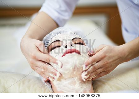 Beautician smears cosmetic mask with hands on face and neck of woman lies on couch in beauty salon.