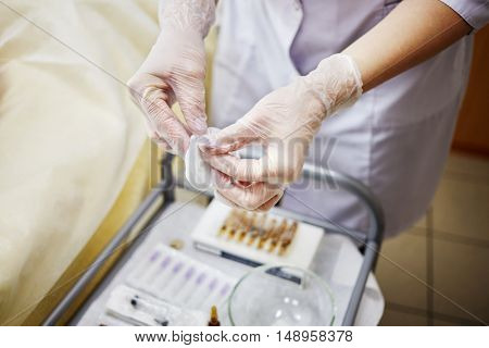 Female hands in rubber gloves hold cotton pad over medical table with ampoules and syringes.