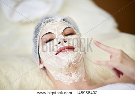 Smiling woman lying on couch in beauty salon with cosmetic mask applied on her face and nech shows goat with her left hand.