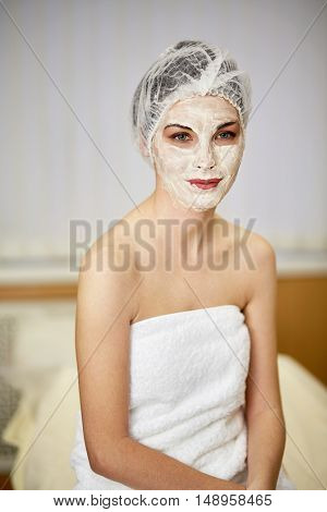 Portrait of smiling woman with cosmetic mask on face and mesh hair cap on head sitting on couch in beauty salon.