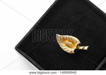 Golden brooch in black jewel box closeup