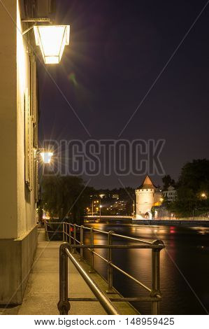 Lights shining on a deserted walkway overlooking the tranquil water of the lake at night Lucerne Switzerland with the city visible in the background