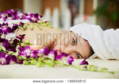 Woman lies on couch among flowers and burning candle in beauty salon, hair wrapped in towel.