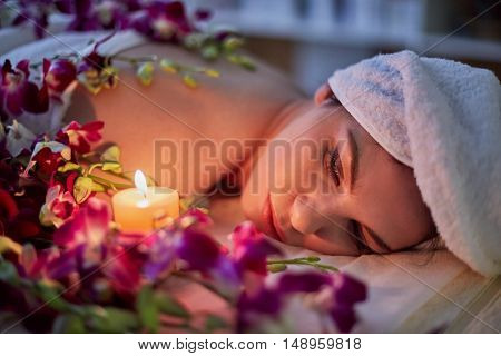 Woman lies on couch with flowers lit by burning candle in beauty salon.