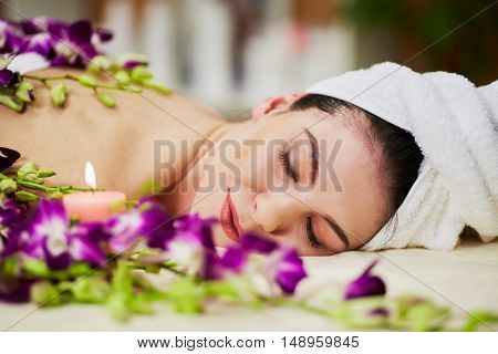 Face of woman that lies with her eyes close on couch among flowers and burning candle in beauty salon.
