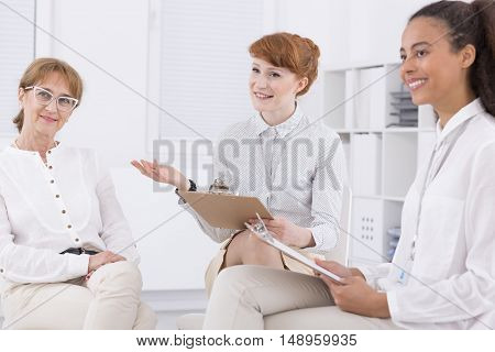 Three elegant woman sitting together and talking about the project