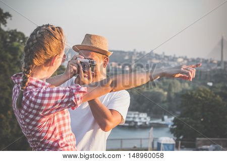 Young trendy guy taking photos of his girlfriend with retro vintage camera in nature. Travel, vacation and love concepts.