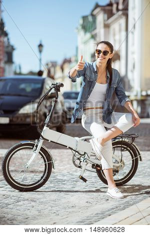 Live with pleasure. Delighted positive smiling woman sitting on the bicycle and thumbing up while expressing gladness