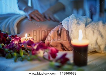 Woman lies on couch with flowers and gets massage lit by two burning candles in beauty salon.
