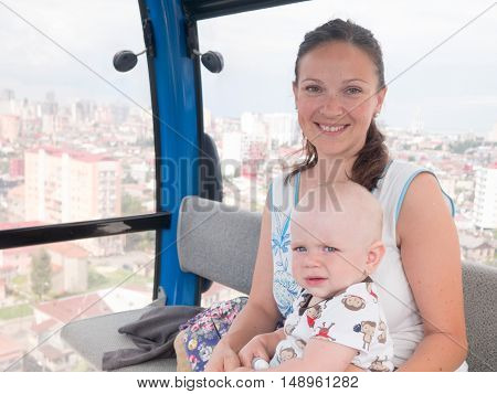 Cute baby and mother rise to the cable car to mountain.