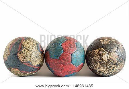 Row of three dirty handball balls isolated on white